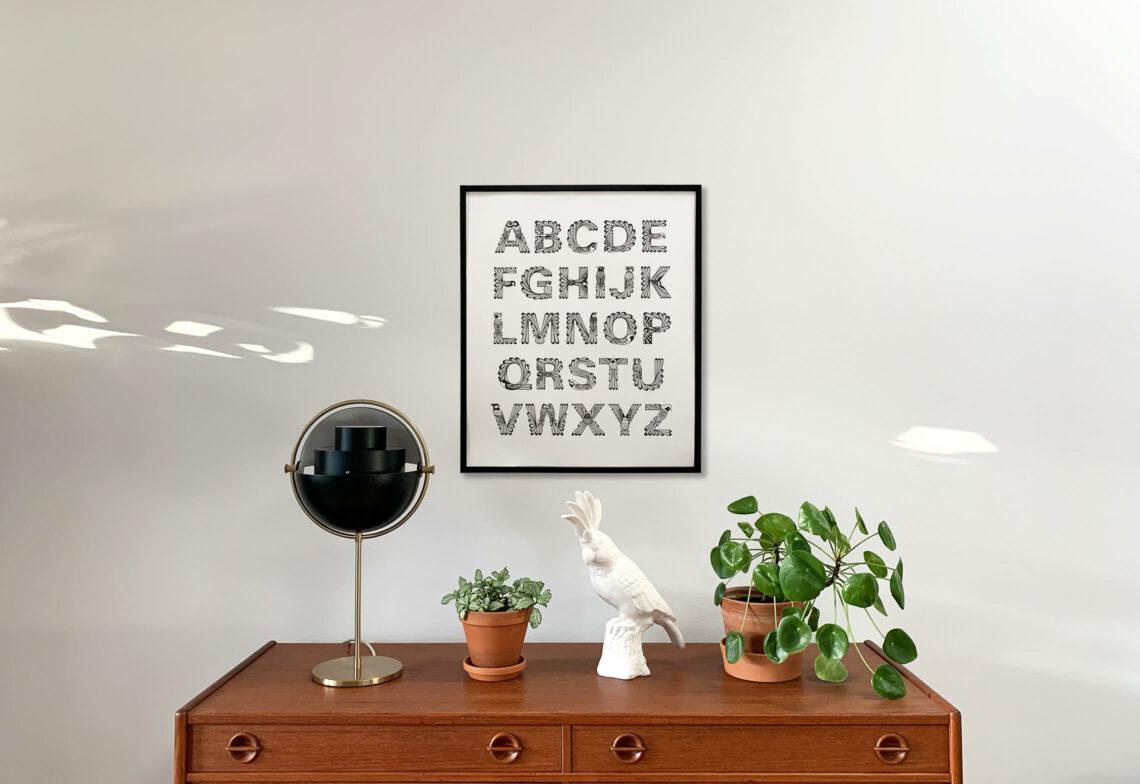"""Inramad affisch av alfabetet """"Ornis"""" hängandes på en vit vägg med en byrå, lampa, växter och prydnadsfågel under affischen"""